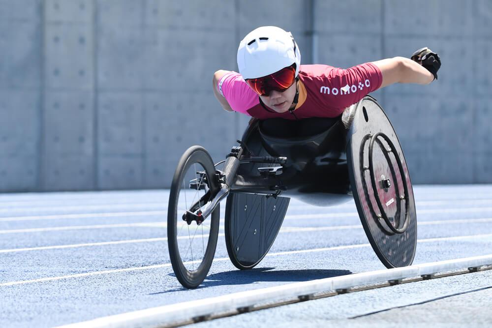 写真:競技場で走る車いすランナー喜納翼選手