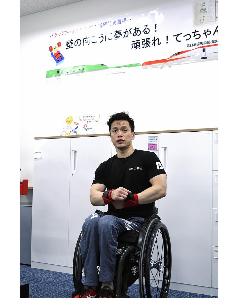 写真:「壁の向こうに夢がある!頑張れ!てっちゃん」と書かれた応援ボードとともに写る西崎哲男選手