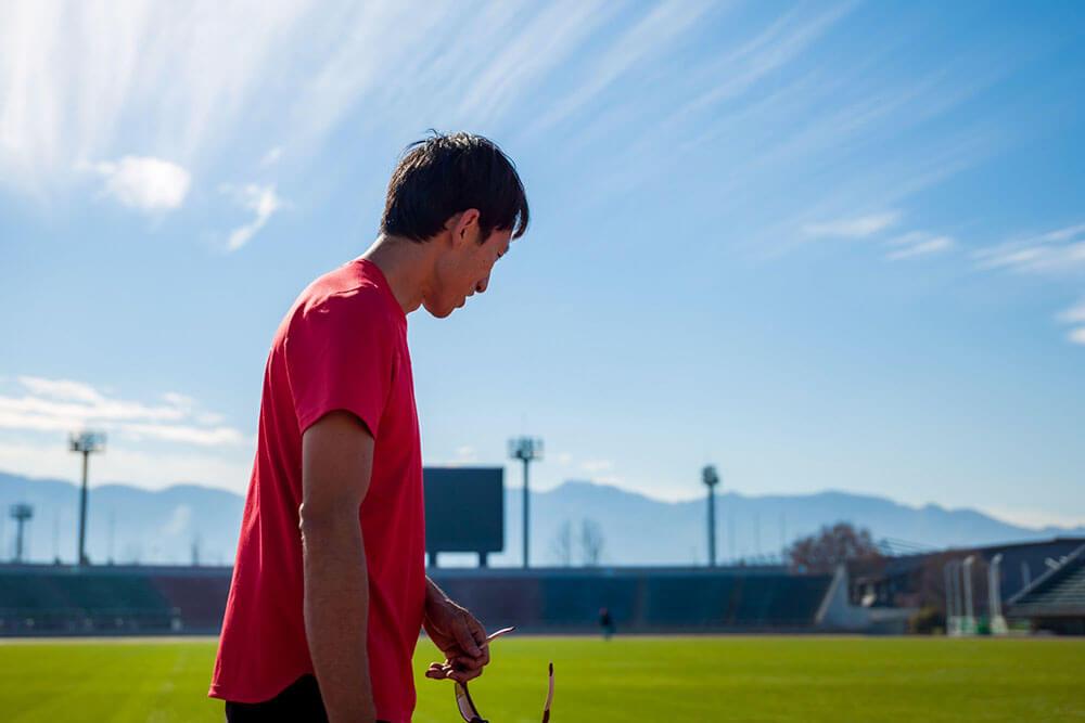 写真:青空の陸上競技場でサングラスを片手に立つ鈴木徹選手