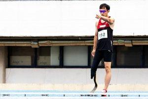 写真:左手を胸の高さまで上げ、まっすぐ前を指さす鈴木徹選手