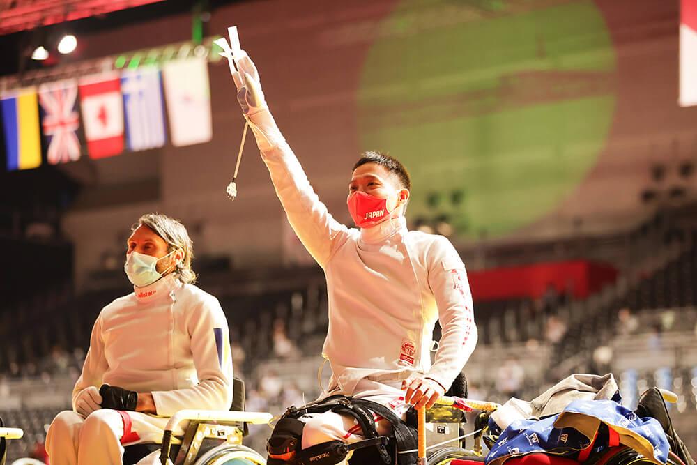 写真:車いすフェンシング日本代表の藤田道宣選手が競技会場で右手を高々と挙げている様子