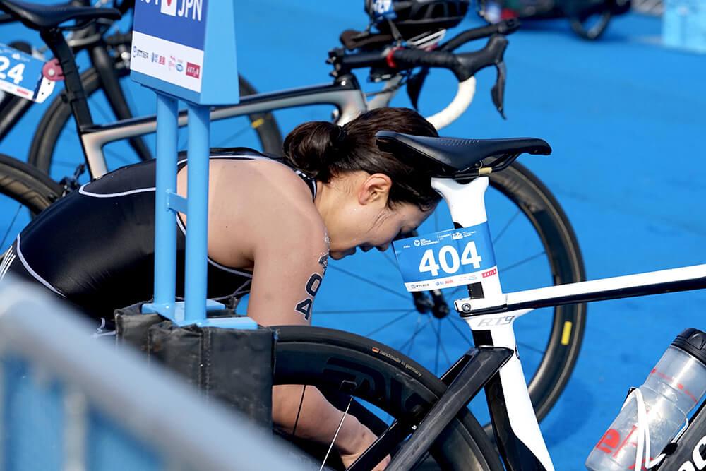 写真:自転車のわきでかがんでいるパラトライアスロン谷_真海選手