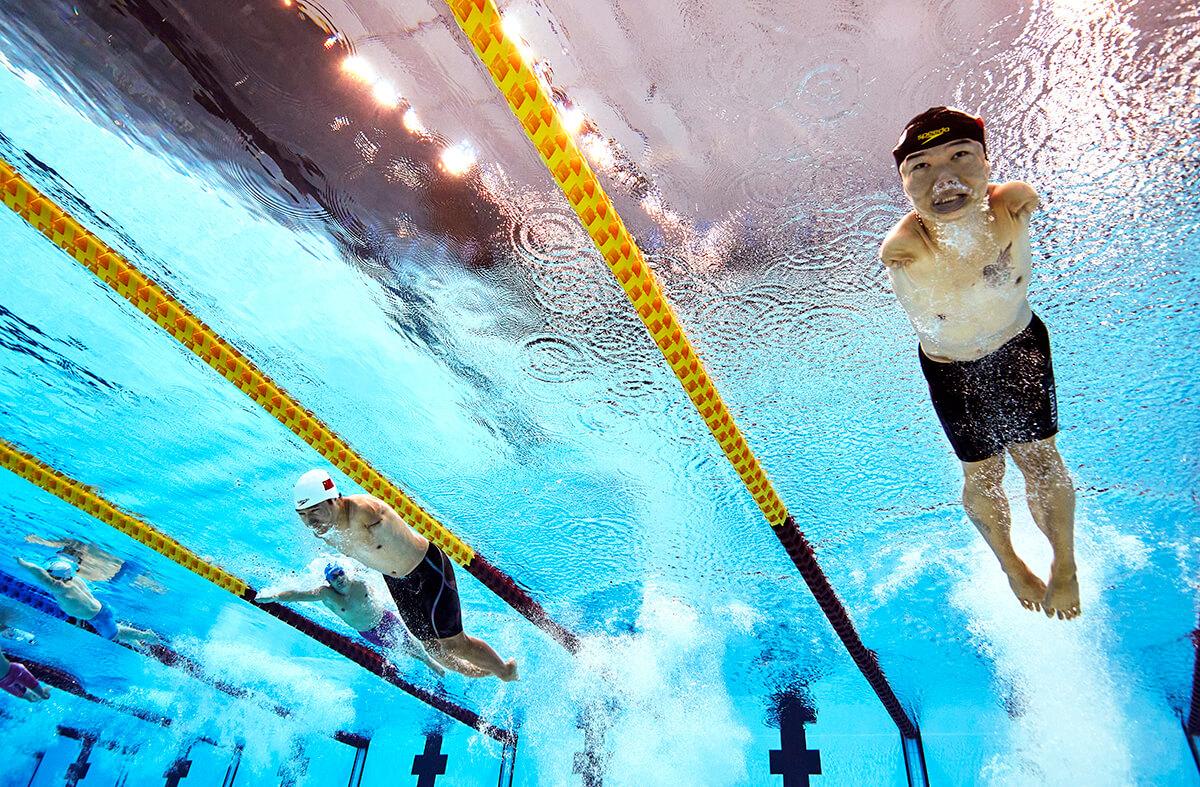 写真:水中の下から上に向けて、中国の鄭濤(チェン・タオ)選手や他の選手たちが泳ぐところを捉えたショット。ゴーグルをしていないチェン選手の目がしっかりと見開いている。