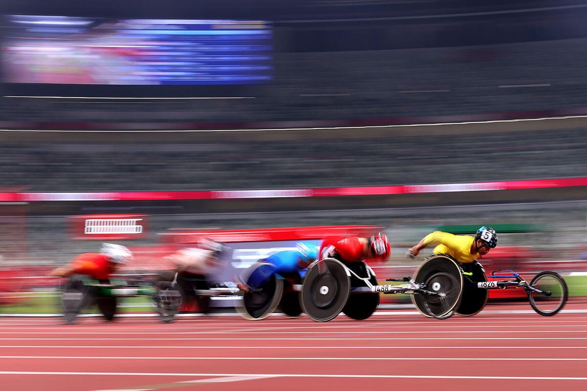 写真:男子5000mT54クラスの予選で、先頭を走るタイ代表プタレット・コンラク選手と他の4人の車いすレーサーが疾走するシーン