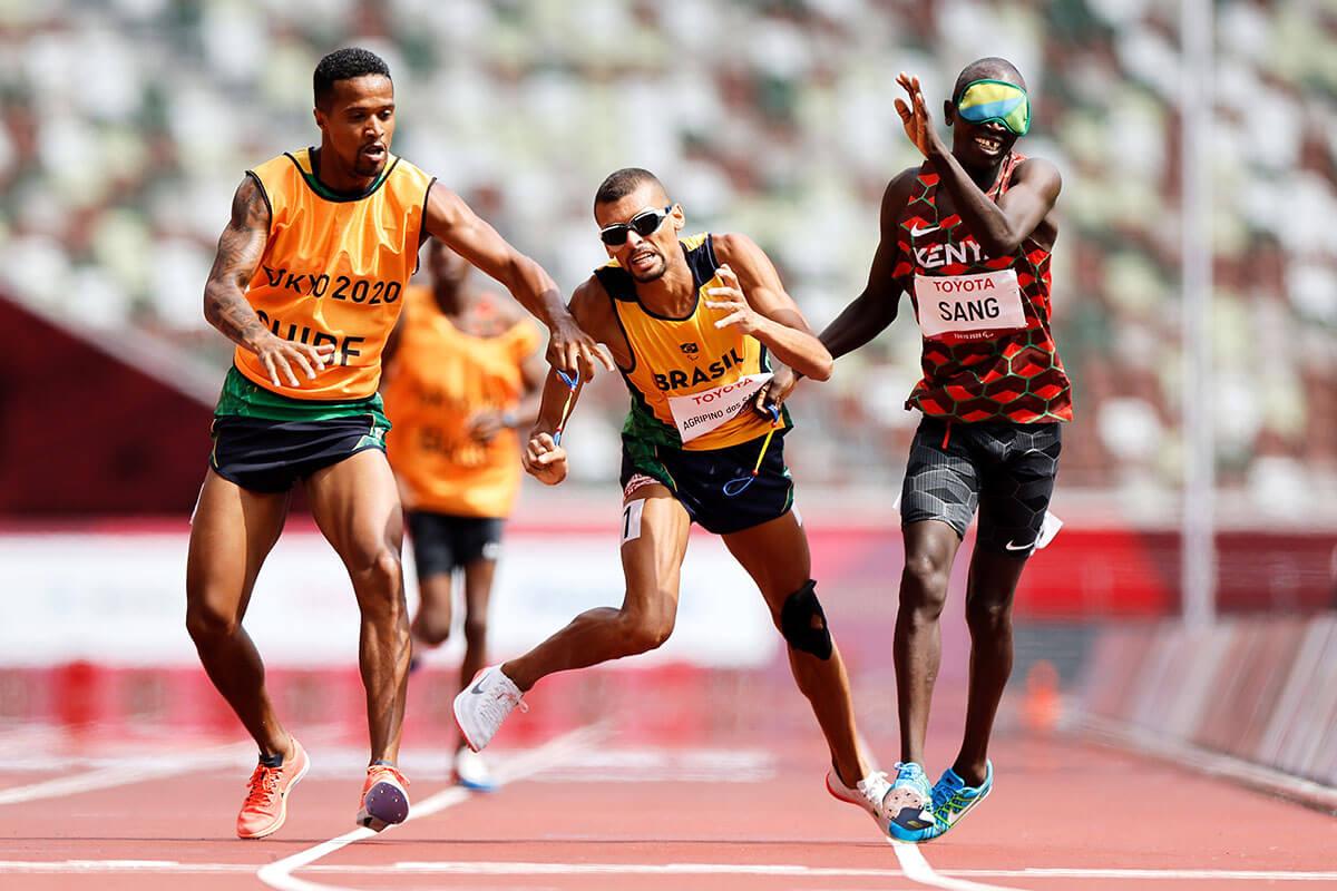写真:国立競技場トラックのゴール直前でガイドに伴われたブラジル選手が、ガイドのいないケニアの選手と接触し倒れそうになっている瞬間