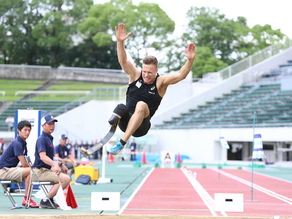 競技場で、両手両足を高く上げ、幅跳びの跳躍を見せるマルクス・レーム選手