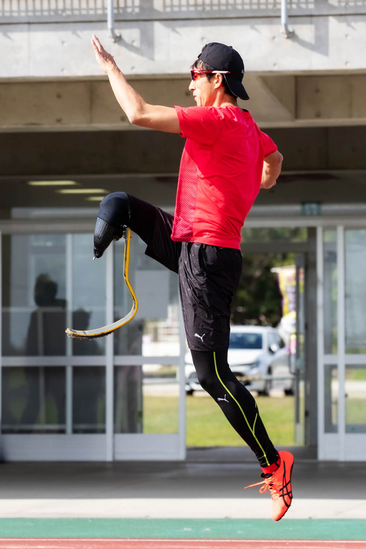 写真:競技場のトラックで跳躍するハイジャンパー鈴木徹選手