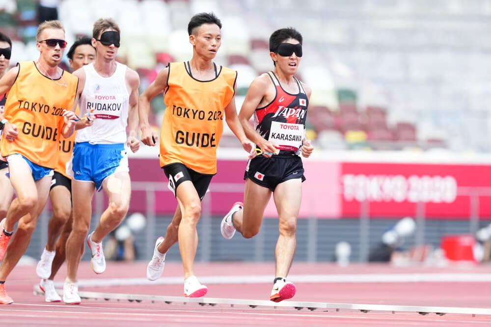 写真:伴走者とともに競技場のトラックを走る全盲のランナー唐澤剣也選手
