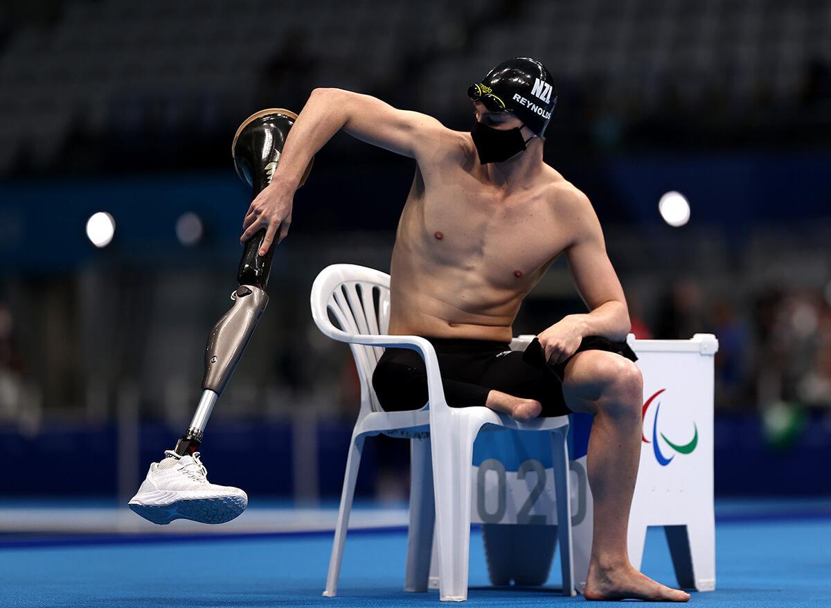 写真:男子200m個人メドレーSM9決勝に向けて準備をするため、プールサイドの椅子に座り義足を手にしているニュージーランドのジェシー・レイノルズ選手