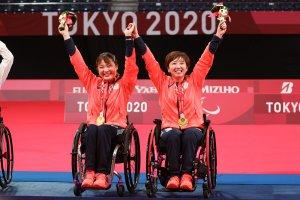 写真::パラバドミントンダブルスでも金メダルを獲得した里見紗李奈選手とペアを組んでいる山崎悠麻選手がメダルをかけ万歳し喜んでいるシーン