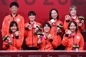 写真:銅メダルとメダリストに送られる花のブーケを手に笑顔のゴールボール女子チームと市川監督