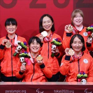 サムネイル画像:銅メダルとメダリストに送られる花のブーケを手に笑顔のゴールボール女子チームと市川監督
